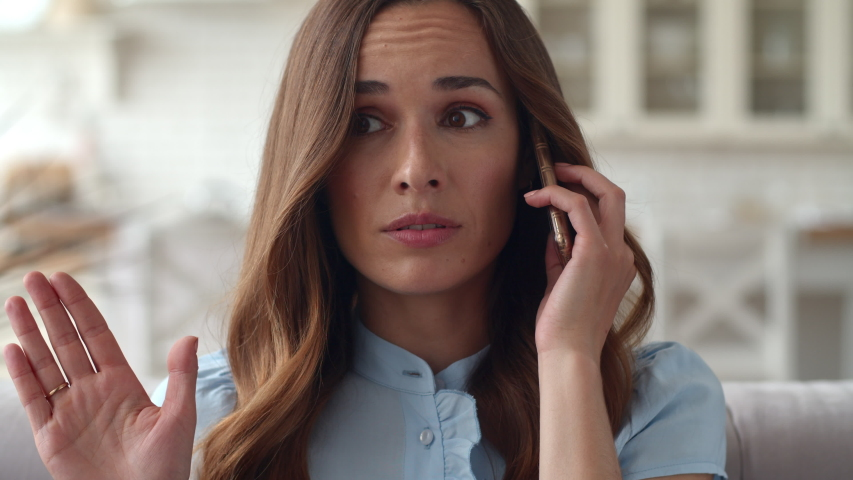 Young business woman having unpleasant conversation on mobile phone at home office. Closeup excited girl gesturing while phone call. Portrait of upset woman talking on cellphone on sofa. Royalty-Free Stock Footage #1044824347