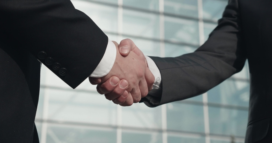 Close up Video of Two Businessmen Shaking hands with each other, Having Successful Deal. Colleagues after business meeting Standing outdoor the office making sign of friendship