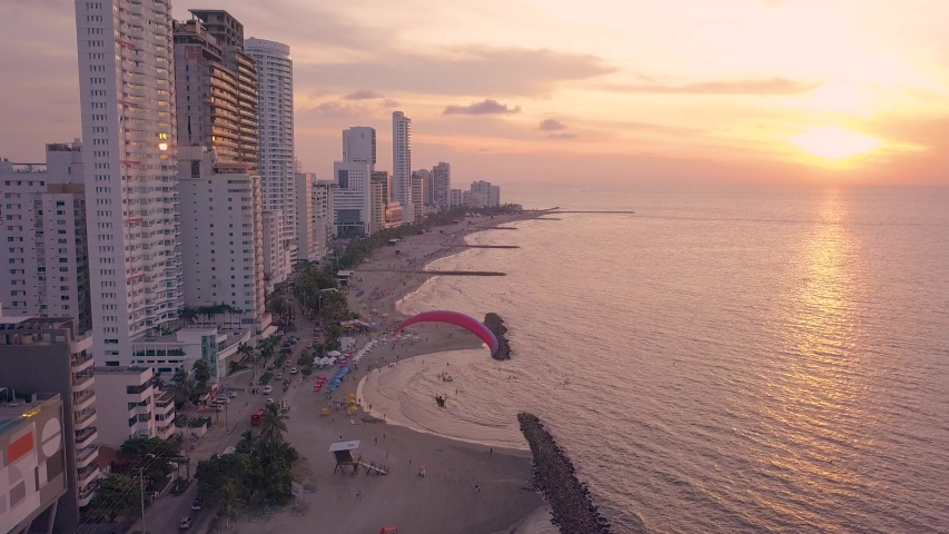 Aerial Drone Shot of Motorized Paraglider/Paramotor flying over Sand Beach of Bocagrande, Cartagena, Colombia next to lots of Skyscrapers & High Rise Buildings into orange Sunset at Caribbean Coast.