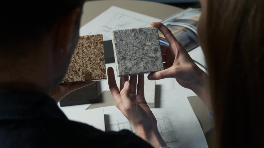 Man and woman choosing material samples close up. Team of architects discussing quartz materials for countertops in the kitchen. Artificial stone examples 4k Royalty-Free Stock Footage #1044831580