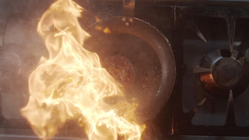 Top view of burger cutlet fried in blazing fire in pan. Slow motion video | Shutterstock HD Video #1044831616