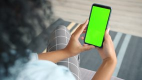 Back view of brunette holding chroma key green screen smartphone watching content without touching or swiping. Gadgets and contemporary people concept.