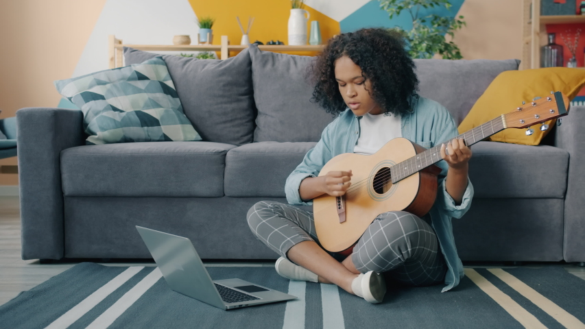Mixed race young woman is learning to play the guitar using laptop computer at home. Girl is looking at screen and playing the musical instrument alone.