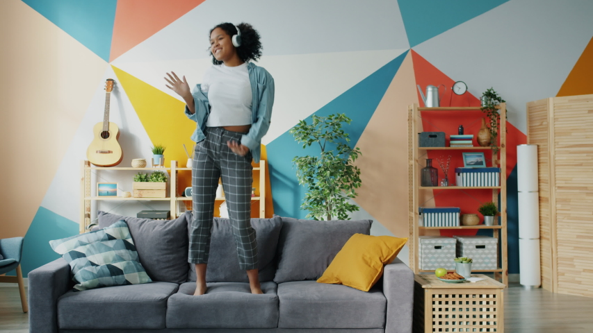 Mixed race woman in headphones is dancing on sofa in apartment having fun alone feeling happy and carefree. Joyful young people and entertainment concept. Royalty-Free Stock Footage #1044836731