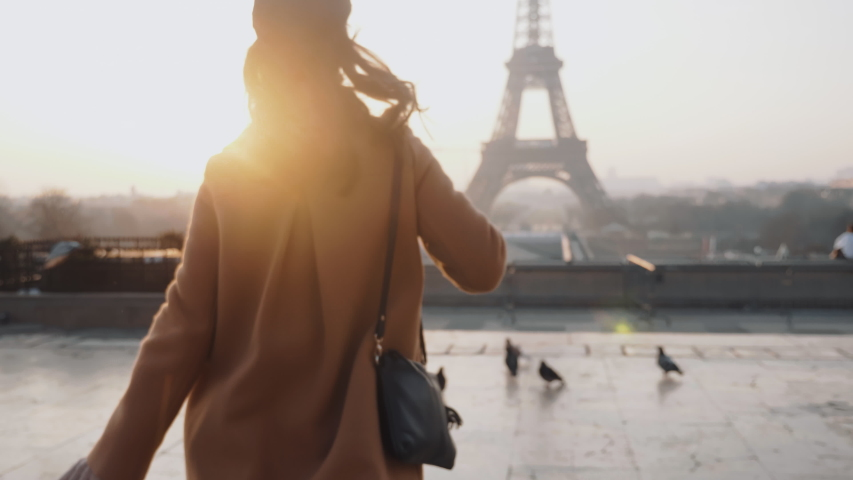 Rear view happy tourist woman running to misty sunrise Eiffel Tower view in Paris on romantic vacation trip slow motion.