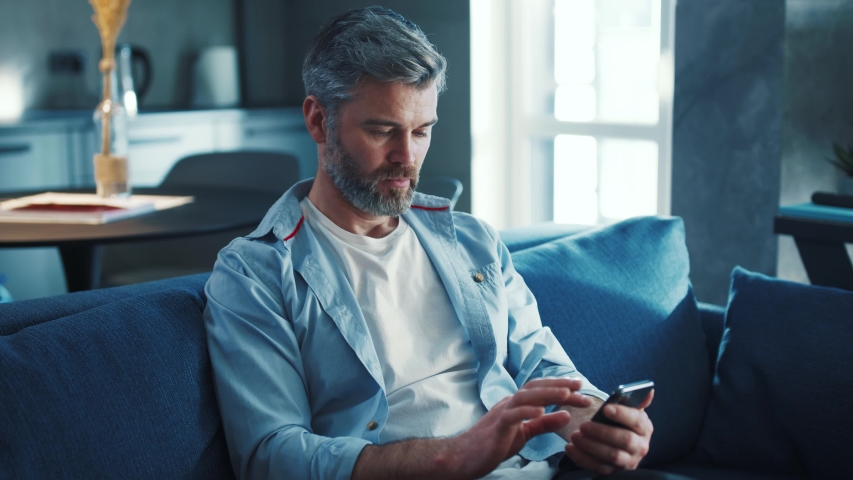Close up view of cheerful middle aged man with grey hair sitting on the sofa using phone smile in the modern apartment texting message scrolling tapping technology isolated lifestyle slow motion | Shutterstock HD Video #1044844771