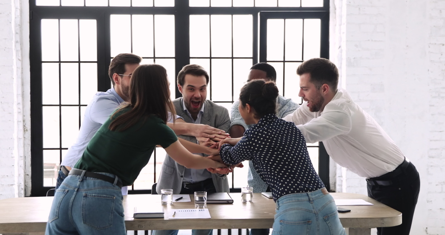 Happy reliable multi ethnic team staff business group stack hands together over meeting table express teamwork concept, strength in professional support, corporate partnership, power of collaboration Royalty-Free Stock Footage #1044846337