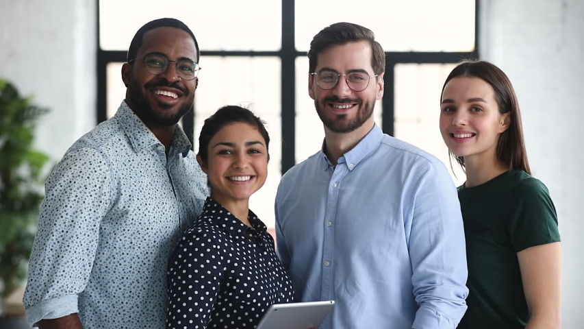 Smiling professional diverse corporate office business team members group look at camera, four happy proud confident multiracial leaders employees staff diverse people group stand together, portrait