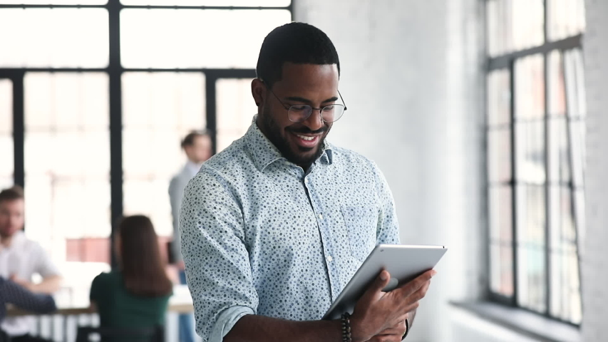 Young professional african businessman worker using digital tablet corporate software standing in office, smiling ethnic male manager working online on pad computer tech in modern company office | Shutterstock HD Video #1044846457