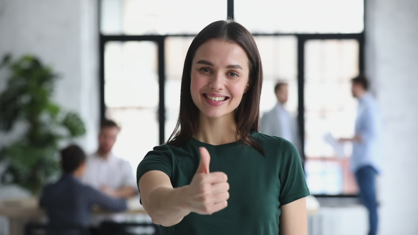 Happy proud confident young professional business woman leader winner employee looking at camera showing thumbs up hand sign gesture in office recommend best job choice concept, closeup portrait