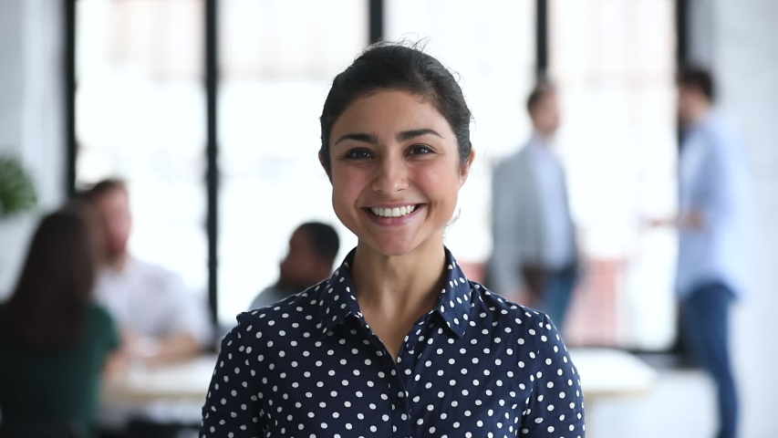 Smiling attractive confident young indian ethnicity business woman looking at camera in modern corporate office, happy millennial hindu girl sales professional intern employee close up portrait