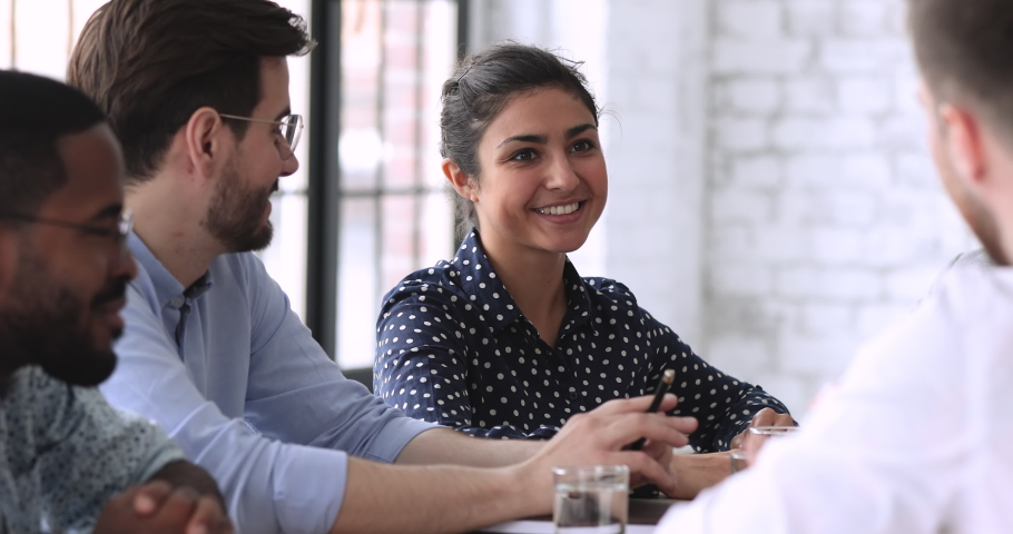 Smiling indian businesswoman hr team member executive talking to male job applicant coworker having professional friendly business discussion during employment interview, group meeting or negotiation