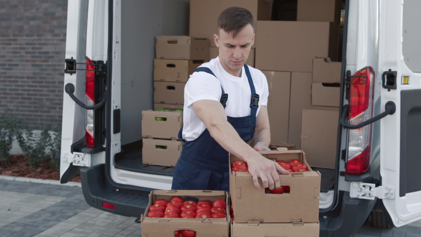 Transportation of Food on Truck. Delivering Order of Foodstuffs from Production Plant for Buy. Worker Carrying and Piling Boxes of Tomatoes for Vendor. Concept of Transfer Company or Carriage on Lorry. | Shutterstock HD Video #1044847210