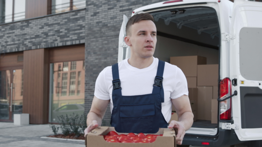 Transportation of Food on Truck. Order of Foodstuffs from Production Warehouse for Sale. Young Worker Carries Boxes of Tomatoes for Provider. Concept of Transfer Company or Carriage on Van or Lorry Royalty-Free Stock Footage #1044847216