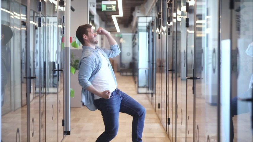 Excited young man employee manager entrepreneur celebrating business success, promotion, professional achievement or reward, dancing alone in modern office, making yes gesture while nobody watching.