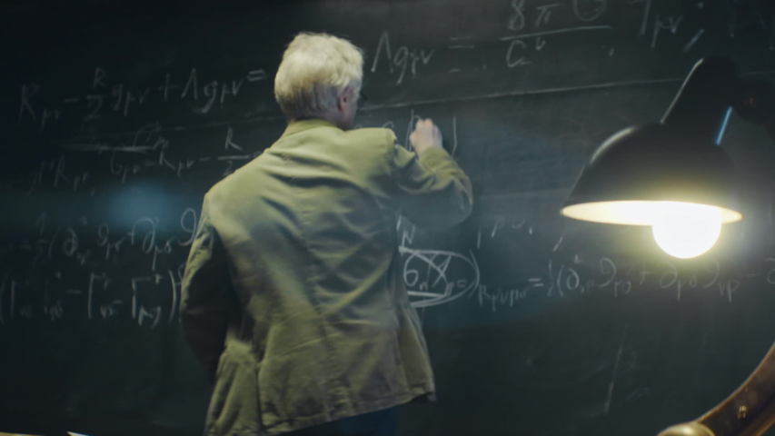 Elderly scientist or Professor is working or researching something late at night. University auditorium, table lamp shines. Anamorphic lens   Shutterstock HD Video #1044855406