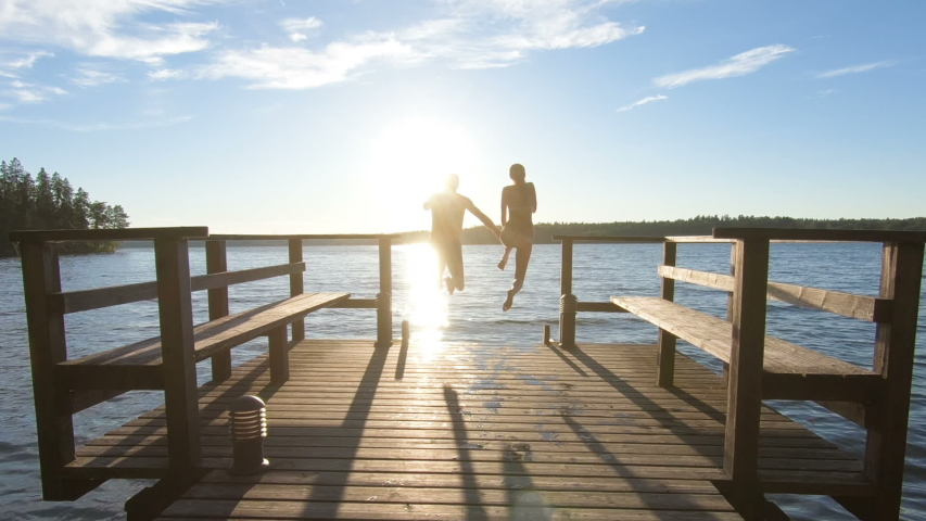 Couple running on a wooden pier and jumping into the lake after the sauna in summer white night in Finland. | Shutterstock HD Video #1044871108