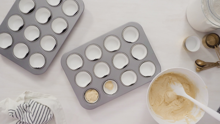 Time lapse. Flat lay. Step by step. Scooping cupcake batter into cupcake liners to bake vanilla cupcakes. | Shutterstock HD Video #1044884536