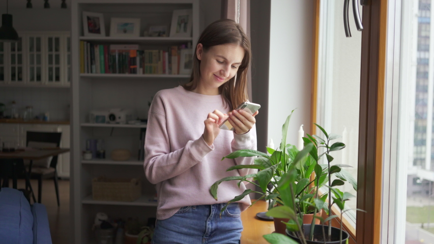 Close up young woman stands near the window at home use phone communication female message cellphone cheerful smile internet modern smartphone portrait. Texting browsing social media. 4k