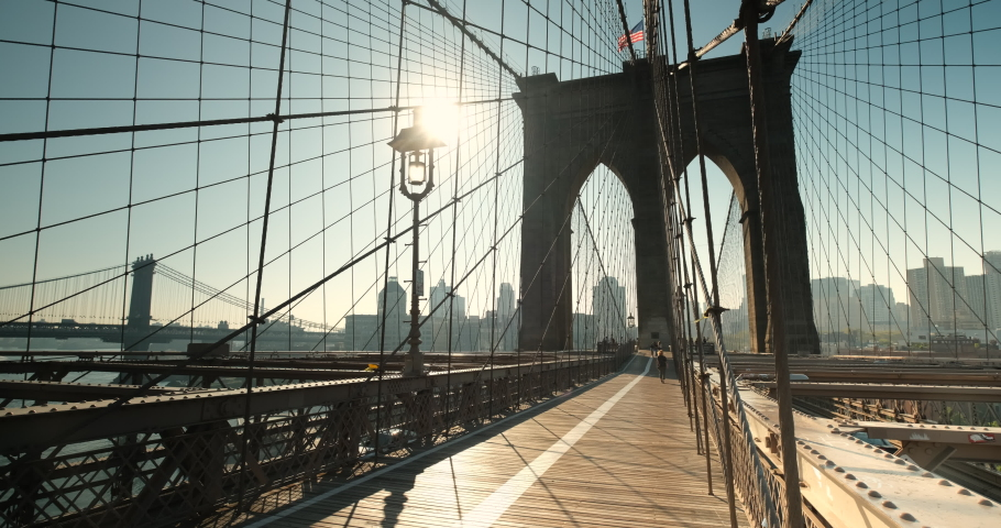 Early morning sun rises on the path of the Brooklyn Bridge over the East River connecting Manhattan New York to Brooklyn USA