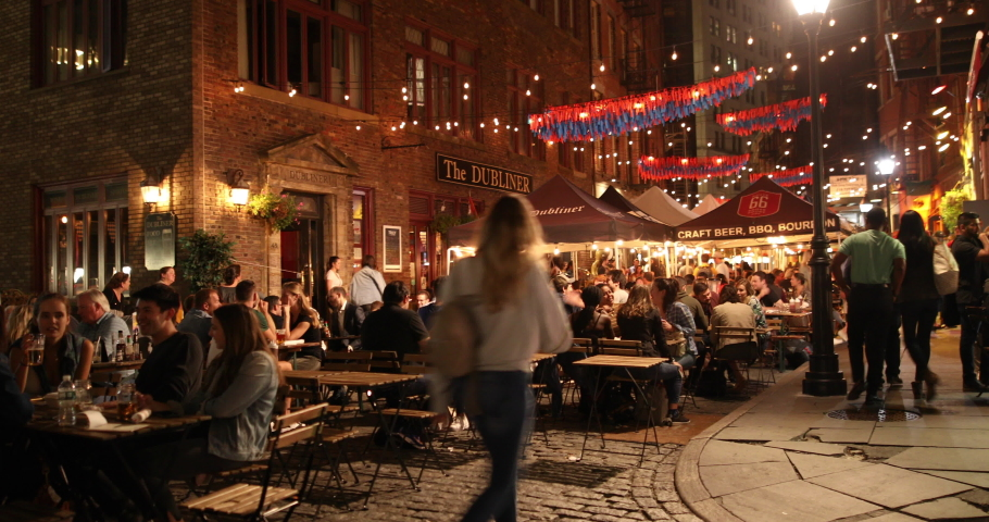 Manhattan, New York - September 20, 2019: People drink and eat by the restaurants and outdoor taverns on historic Stone Street in lower Manhattan in New York City USA.