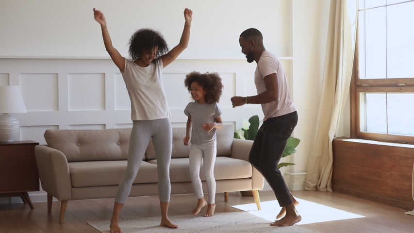 Overjoyed smiling african ethnicity family couple dancing with cute daughter at living room. Happy mixed race family having fun, involved in funny activity together on weekend morning at home. Royalty-Free Stock Footage #1044920755