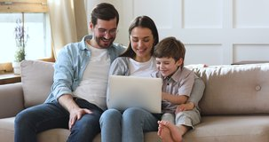 Happy family young parents couple and cute preschool kid son using laptop looking at computer screen enjoying watching funny social media video doing online shopping relaxing on sofa at home together