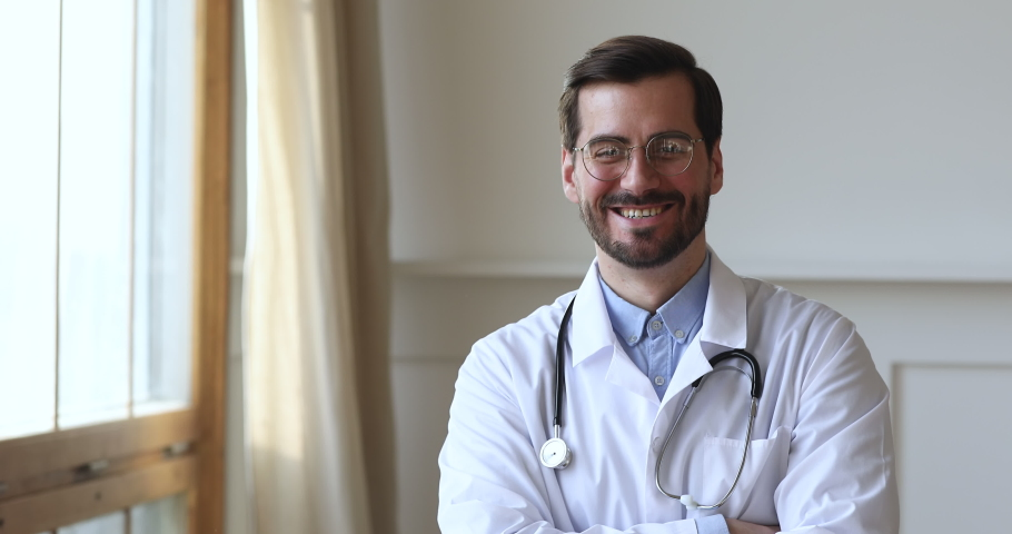 Smiling young man professional medic doctor wear white medical uniform glasses looking at camera standing in hospital office, happy friendly male gp physician surgeon doc close up view portrait