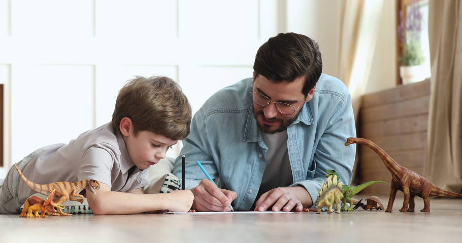 Caring young adult father playing with preschooler child son help teach drawing pencils enjoy single parent and little kid creative lifestyle activity together lying on warm floor at home apartment