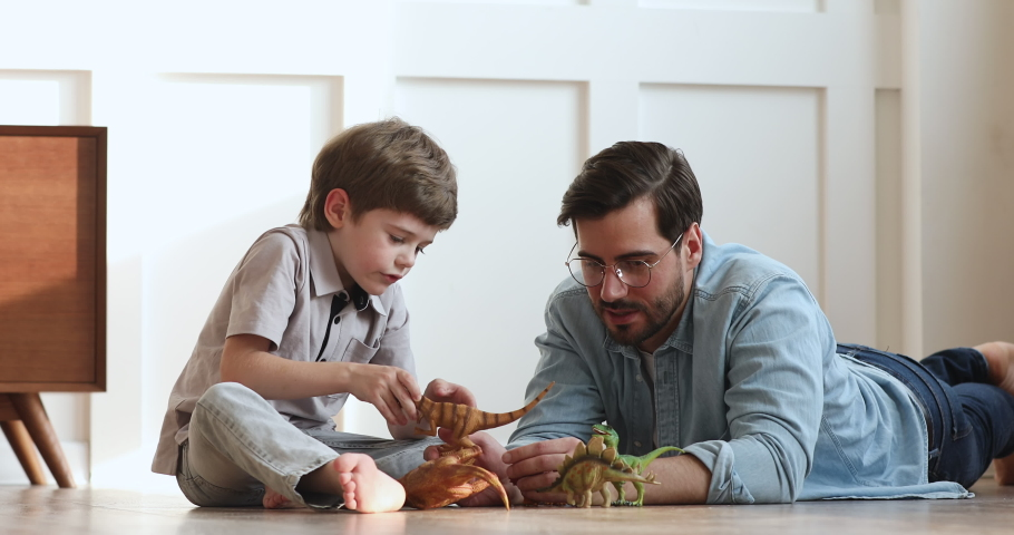 Loving young adult dad and cute preschool child son talking playing dinosaurs toys sit on warm floor, happy single parent father helping little kid explain paleontology having fun at home together