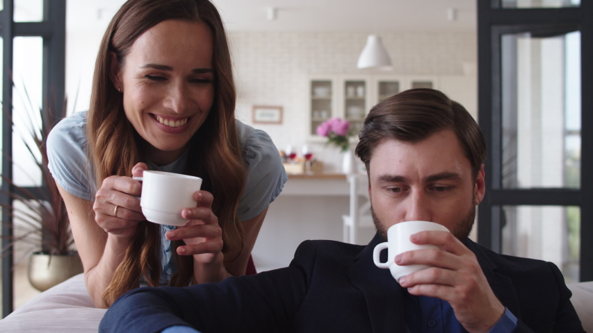Closeup smiling couple drinking tea at home together. Happy woman bringing cups of tea for husband in living room. Portrait of joyful couple taking coffee break on sofa in slow motion. Royalty-Free Stock Footage #1044935296