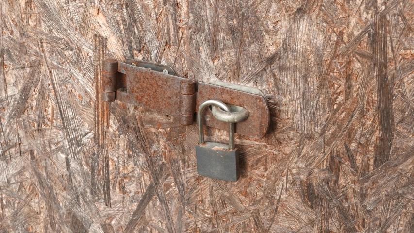 4K Padlock on Worn Plywood Door | Shutterstock HD Video #1044955669