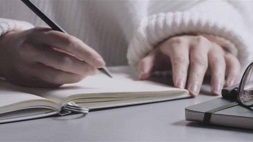 Closeup of a young woman writing in a white notebook. Education, business, working from home concept.  Royalty-Free Stock Footage #1044957388