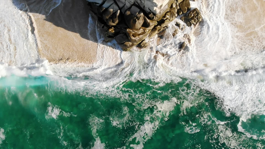 Large waves crash onto rocks and beach in this slow motion drone shot looking down on the breathtaking turquoise water in Baja California Sur