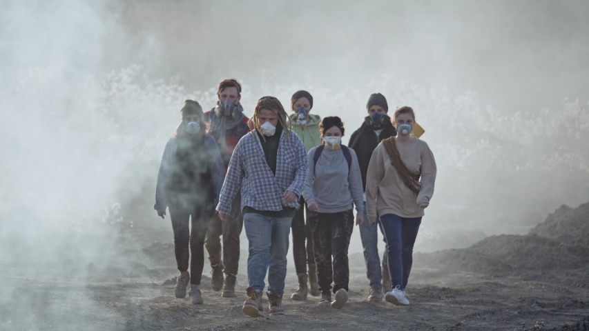 Group of young people in gas mask going through the toxic smoke in a desolate landscape. Royalty-Free Stock Footage #1044976150