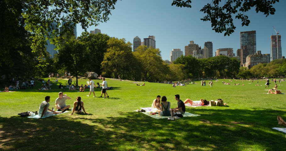 Manhattan, New York - September 21, 2019: People relax on the green lawn of the Sheep Meadow by the apartment and condominium skyscraper residences over the Manhattan skyline in Central Park