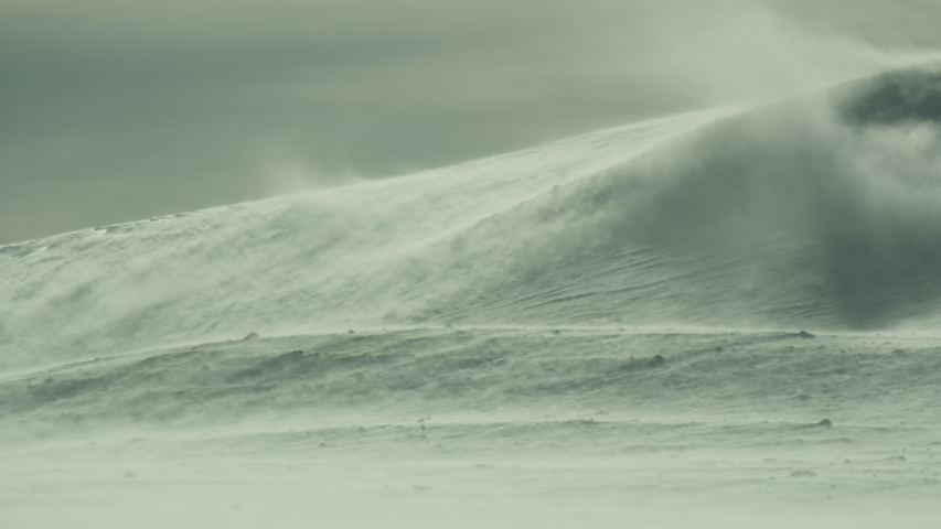 Rigorous blizzard over snow covered hills in Antarctica.