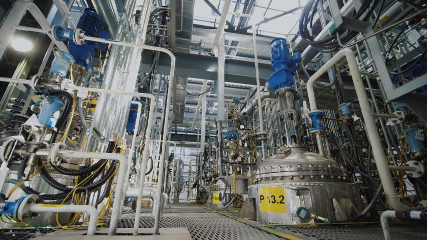 Refinery factory inside. Modern equipment, steel tanks and boilers with cables, pipelines and valves for chemical mixing. Production of anti-turbulent additives used in oil industry