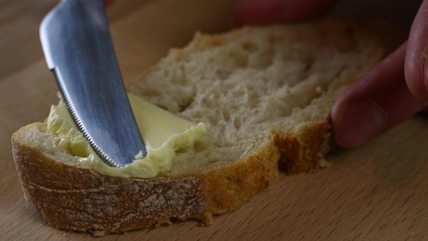 Man spreads butter on bread with a knife | Shutterstock HD Video #1045018201