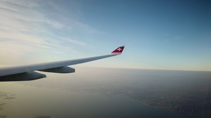 Zurich, Switzerland - Jam 15, 2020: Airplane window view out of Swiss Airlines flight with Swiss Logo and wing. Point of view of traveller. Blue sky and horizon.