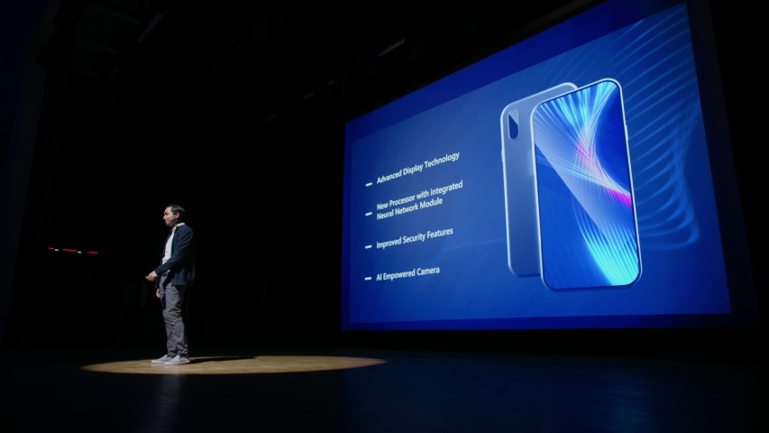 Live Event with Brand New Products Reveal: Keynote Speaker Presents Smartphone Device to the Audience. Movie Theater Screen Shows Mock-up Touch Screen Mobile Phone with High-Tech Features, Highlights Royalty-Free Stock Footage #1045029574