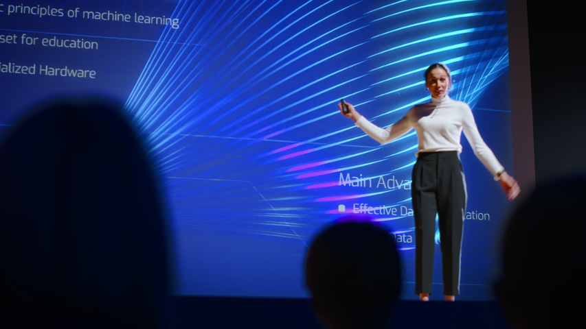 On Stage, Successful Female Speaker Presents Technological Product, Uses Remote Control for Presentation, Showing Infographics, Statistics Animation on Screen. Live Event / Device Release. Slow Motion