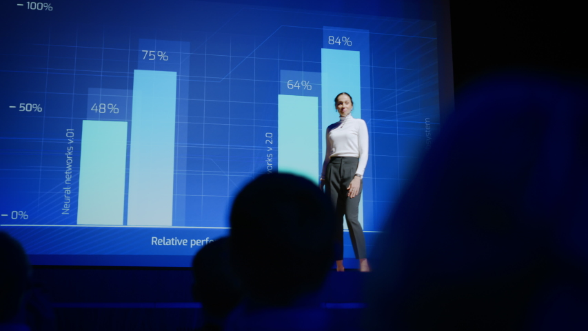 On-Stage Successful Female Speaker Presents Technological Product, Uses Remote Control for Presentation, Showing Infographics, Statistics Animation on Screen. Live Event. Press Conference
