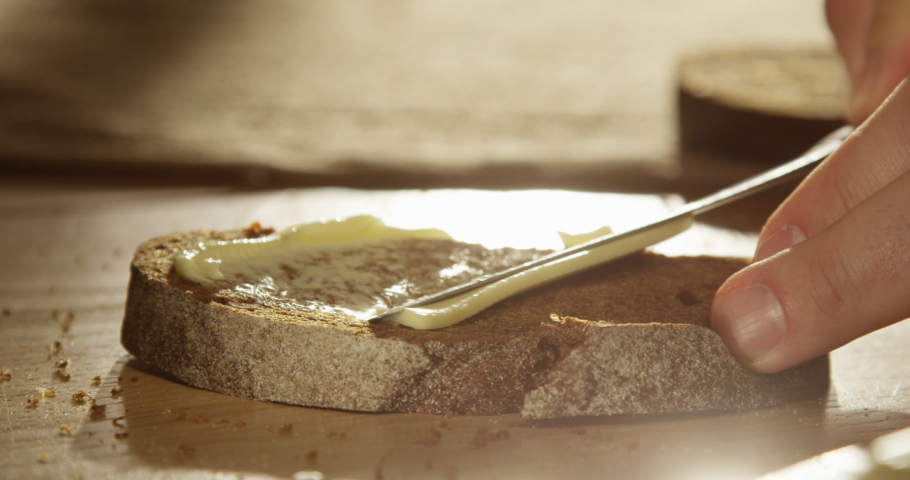 Spreading Butter on Fresh Artisan Rye Bread Slice with a Knife Close up of a Palm on a Wooden Table with Sunshine and Sun Flares Shot on Red Epic | Shutterstock HD Video #1045038649