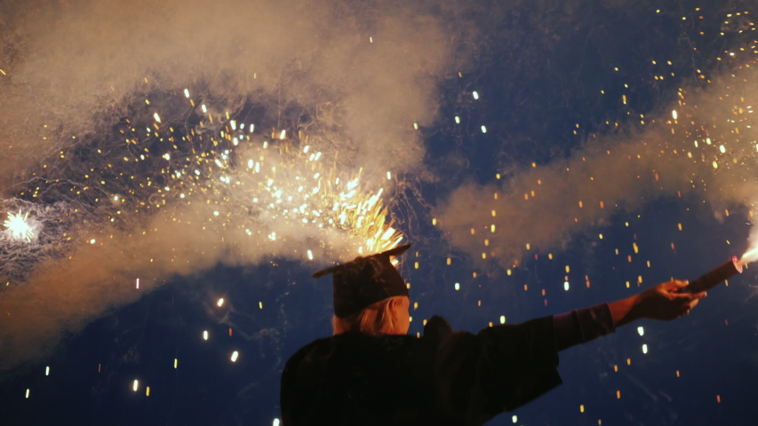 An emotional college graduate in a mantle and a graduation cap with two fireworks in his hands Royalty-Free Stock Footage #1045039942