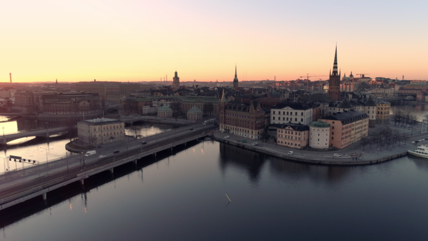 Stockholm city center at sunrise aerial view. Drone shot flying over water and bridge with driving trucks and cars. High angle view of Riddarholmen Old Town skyline at dusk. Capital of Sweden Royalty-Free Stock Footage #1045055563