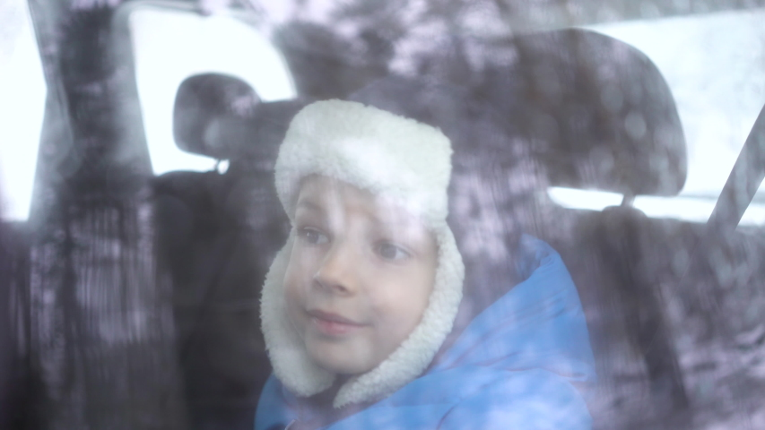 Little boy rides in the car in the back seat in winter forest and looks out the window.