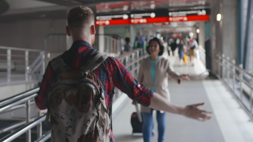 Young hipster man meeting his senior mother in airport walkway. They are greeting each other and hugging. Happy reunion of aged woman and her adult son.