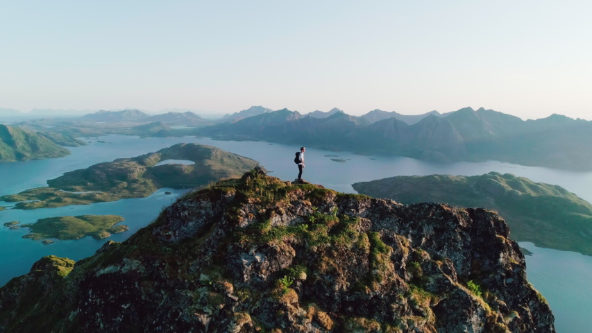 4K slow motion drone shot with orbit motion of young Norwegian climber with backpack standing on top of tall cliff admiring the panoramic sunset view in Lofoten Vesterålen in Norway. | Shutterstock HD Video #1045086502