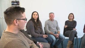 4K: Support group therapy - People sat in circle for a recovery meeting - One man talks while the others listen.  -4K Stock Video clip footage